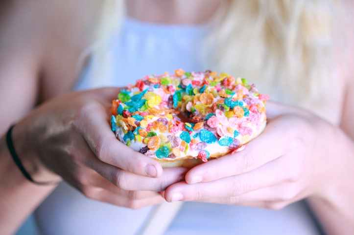 person holding doughnut with toppings